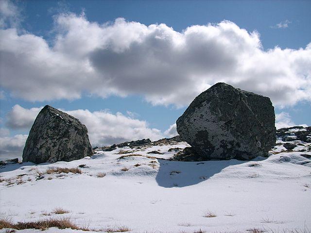 Zwei schwarze kantige Felsen auf einem verschneiten Hang.